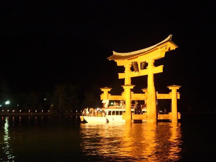 ライトアップされた厳島神社の大鳥居を通過する船を撮影した写真