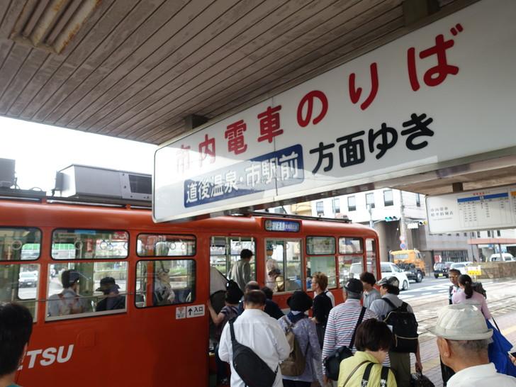 松山市内を走る路面電車に乗る様子を撮影した写真