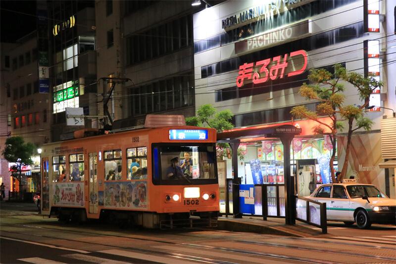 観光通り前に停車する路面電車の写真
