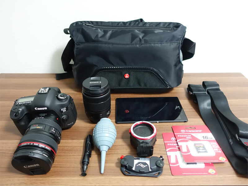 マンフロットのアドバンスメッセンジャーとカメラ用品を並べた写真