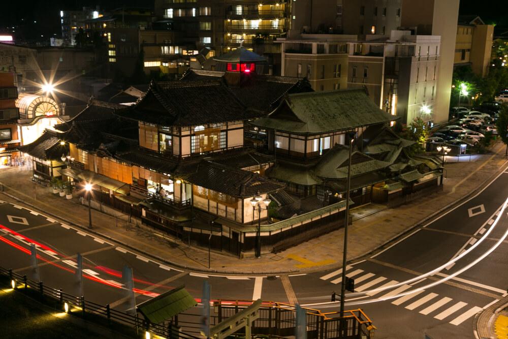 ガス灯で美しくライトアップされる道後温泉本館の写真