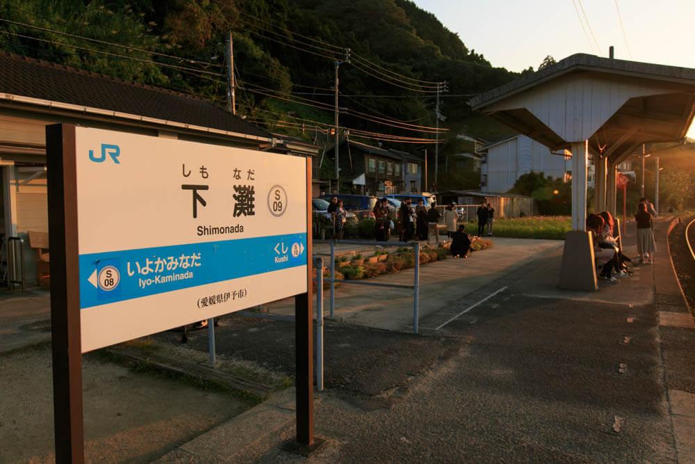 夕日で朱く染まる下灘駅の看板の写真