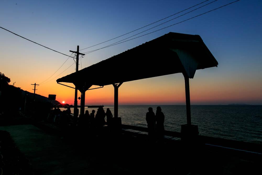 夕日と下灘駅の上屋を撮影した写真