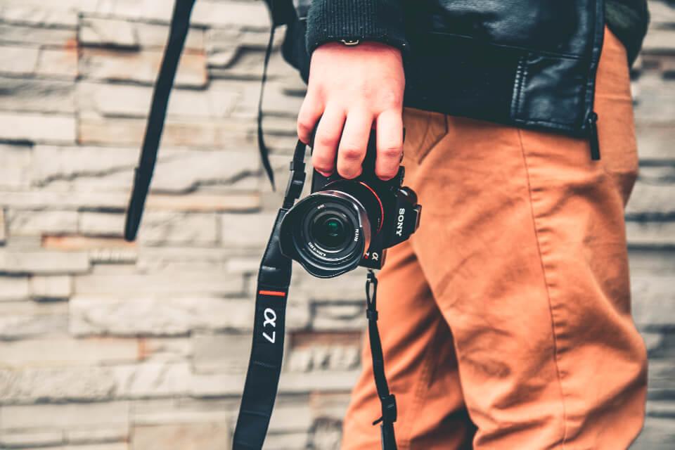 カメラを撮り歩く男性の写真