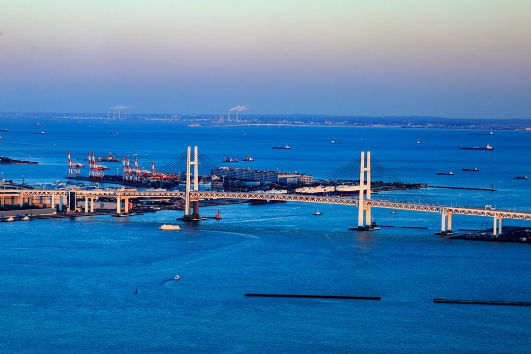 横浜ランドマークタワーから撮った夕暮れ時の横浜ベイブリッジの写真