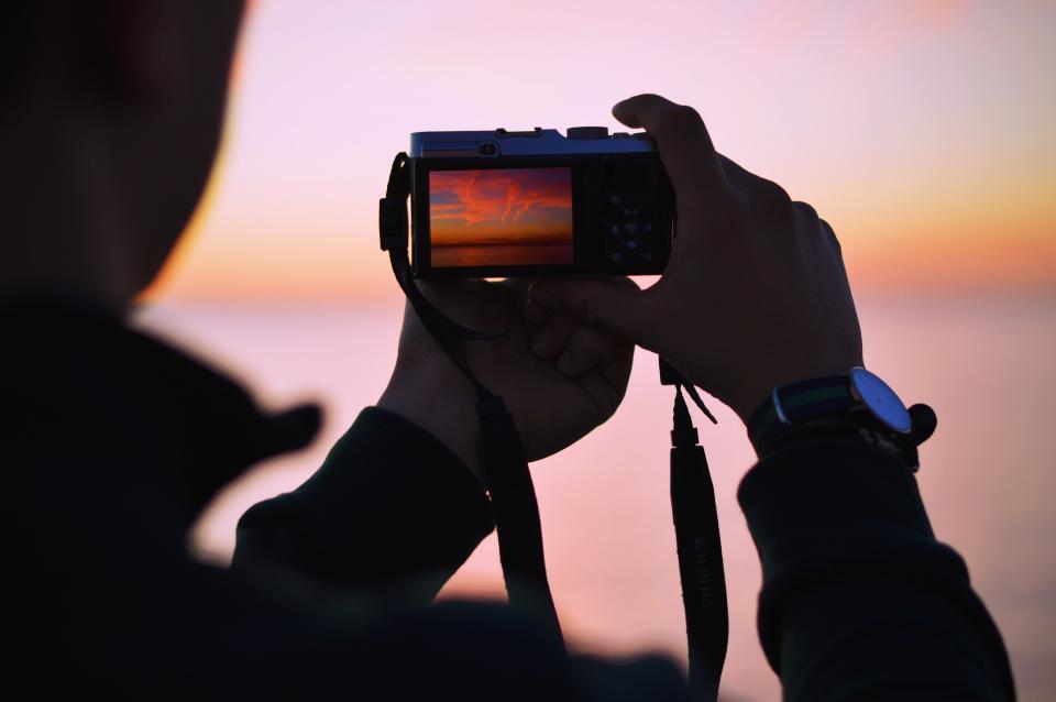 手持ちで夜景を撮影している様子を撮影した写真