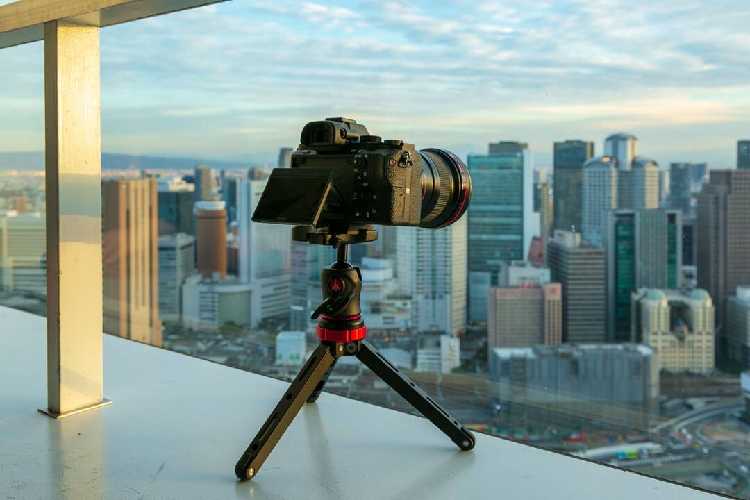 DECADEの卓上三脚にフルサイズ一眼レフカメラを載せて展望台から夜景を撮っている様子