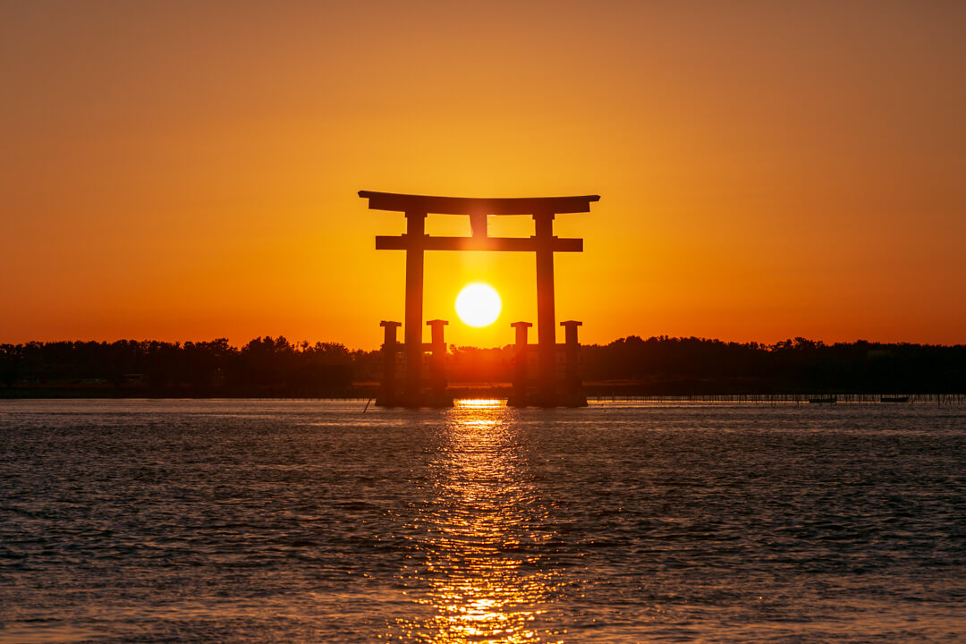 弁天島海浜公園から撮影した鳥居と夕日の写真