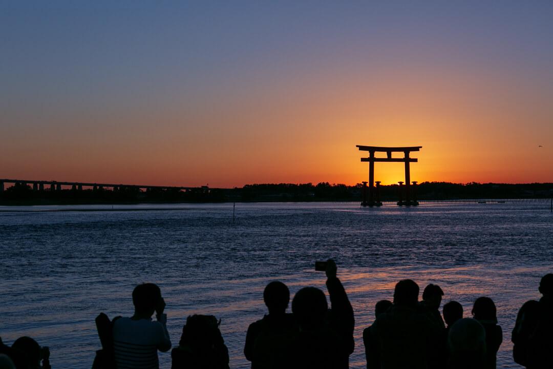 弁天島海浜公園で鳥居を撮るカメラマンの姿を撮影した写真