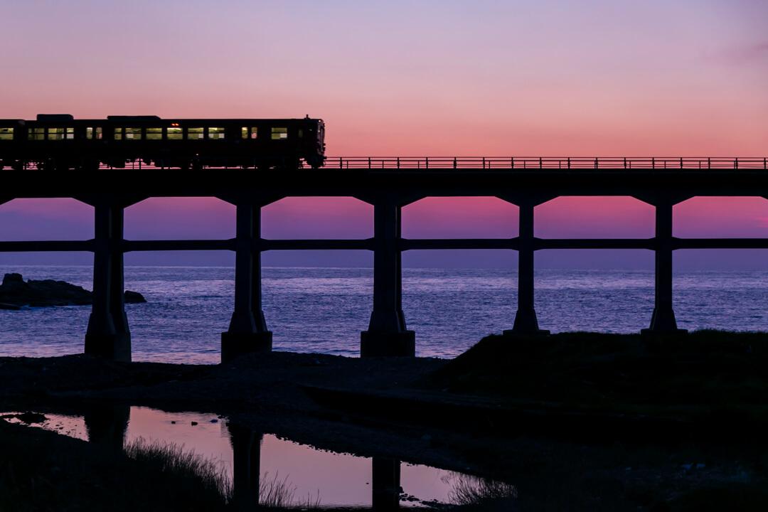 黄昏時に惣郷川橋梁の上を走る列車の写真