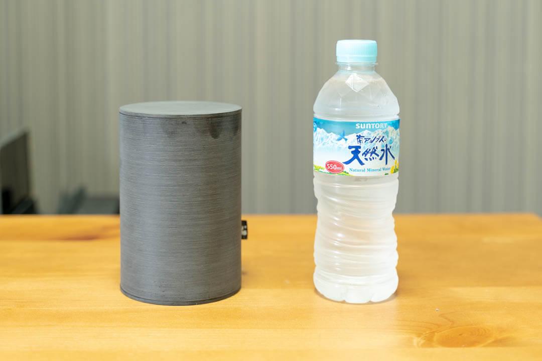 「NuAns CADDY」の大きさをペットボトルと比較している写真