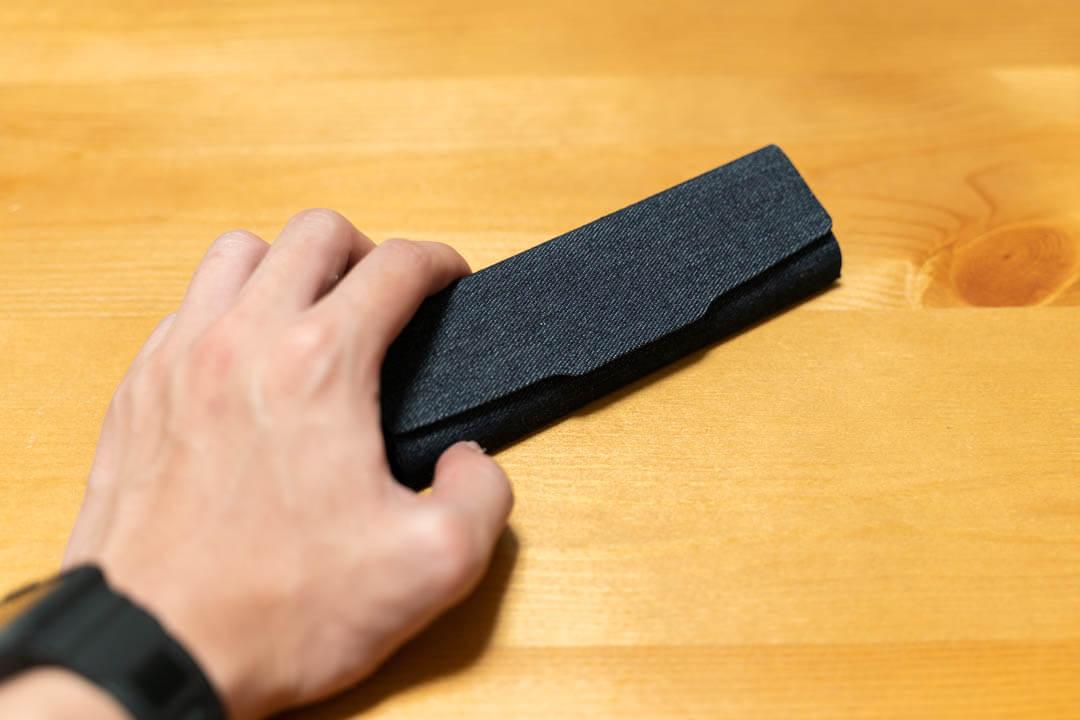 メイガンの三角タイプメガネケースを手で触る写真