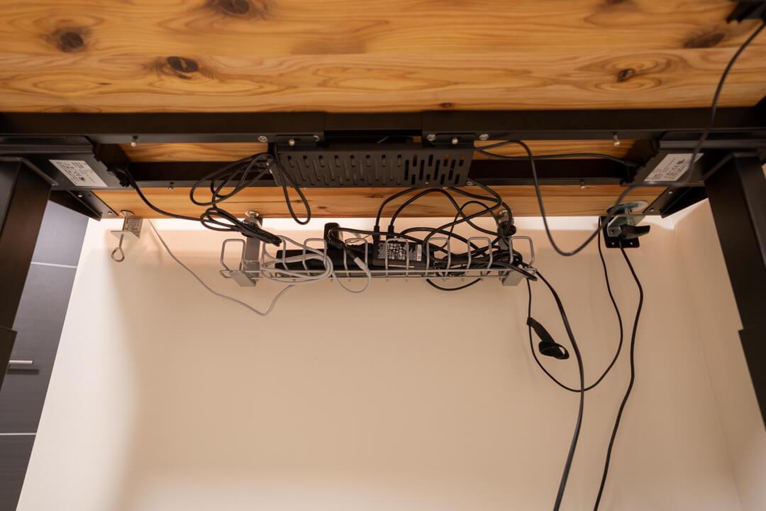PCデスクの配線周りを整える様子