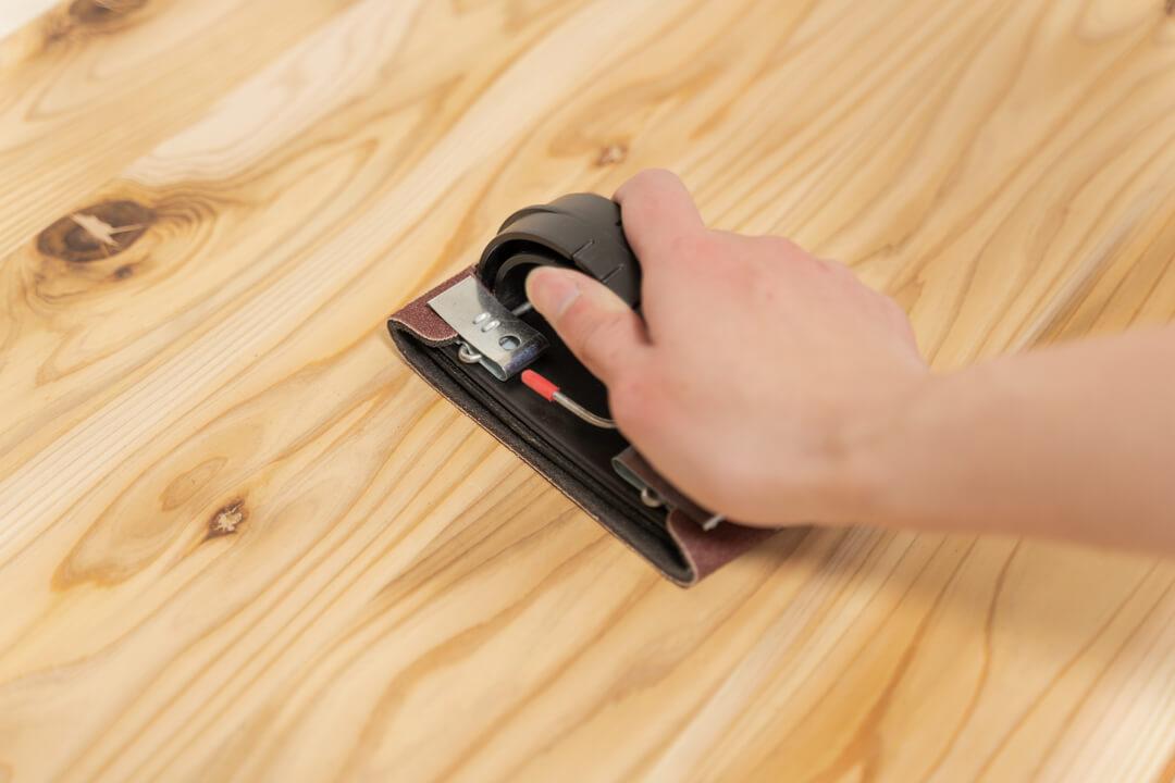 杉無垢ボードを紙やすりで削る様子